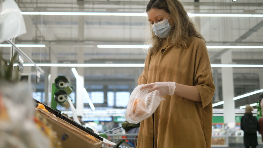 Woman in a medical mask and gloves carefully selects oranges in a grocery supermarket. Protection from the coronavirus epidemic, increased immunity with fresh fruit. Healthy food for fighting viruses.