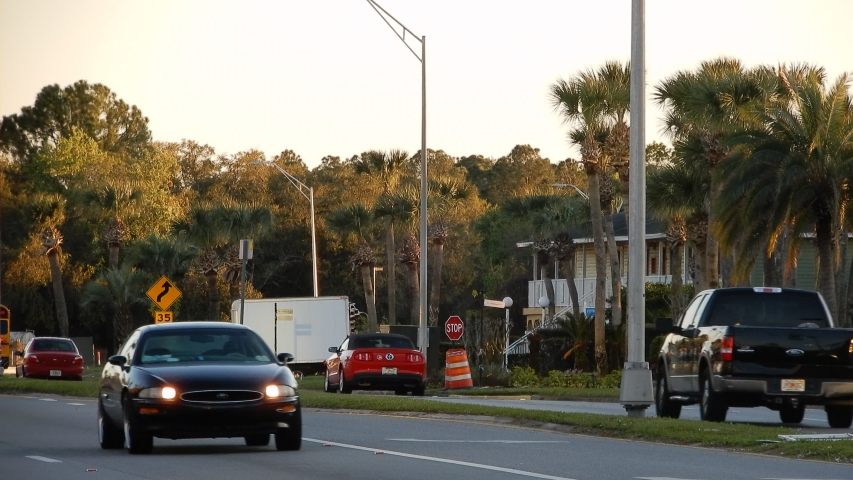 Man On Cellphone Walking Down Road As Yellow School Bus Children Elementary School Drives By At Sunset In Sunny Florida