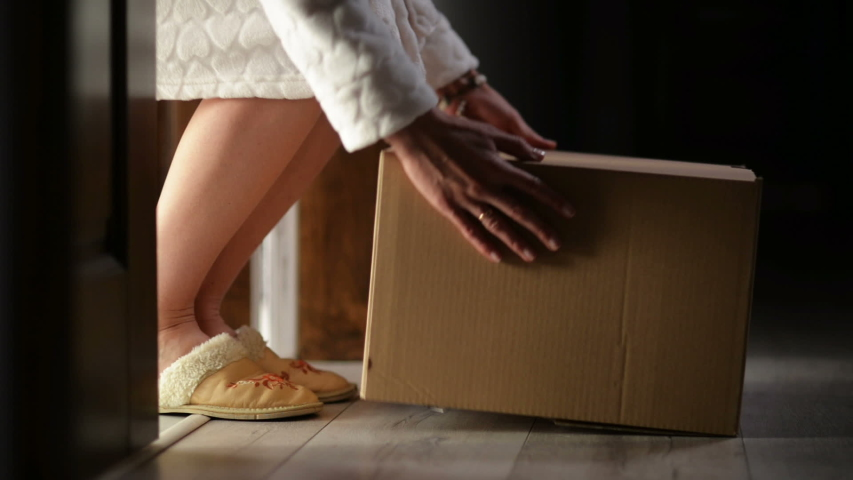 Woman opens the front door and takes a large cardboard box. | Shutterstock HD Video #1049020561