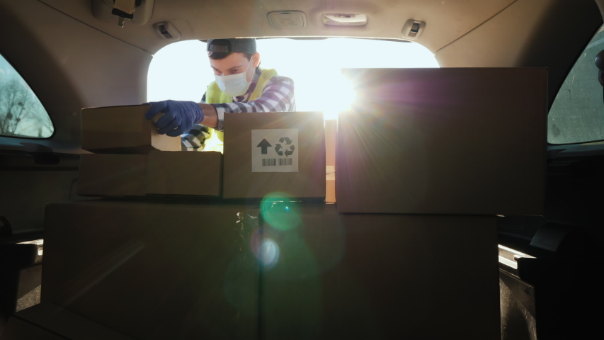 A person in a mask puts boxes in the trunk of a car. Volunteer work in the midst of an epidemic
