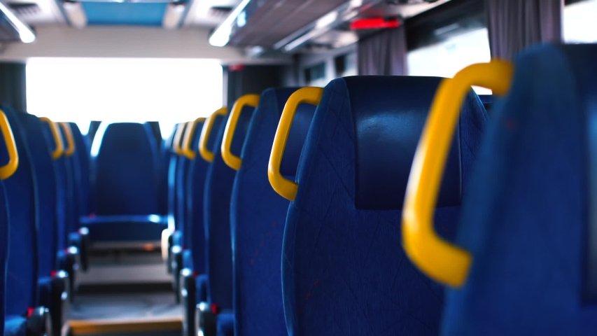Transmission of coronavirus COVID 19 in public transport. Yellow handrails in an empty moving bus during quarantine. Blue color of seats, perspective. Public transport. | Shutterstock HD Video #1049023264