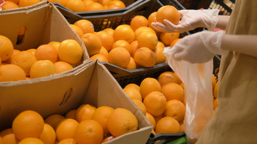 A young woman carefully selects fresh oranges in a supermarket in rubber protective gloves and puts them in a plastic bag. Personal protective equipment against coronavirus. | Shutterstock HD Video #1049026693