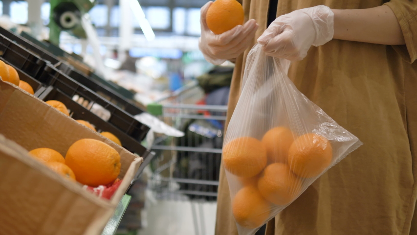 A girl in a supermarket selects fresh oranges in rubber gloves and puts them in a plastic bag. Healthy nutrition to increase immunity. Protective measures against the coronavirus pandemic. | Shutterstock HD Video #1049026696