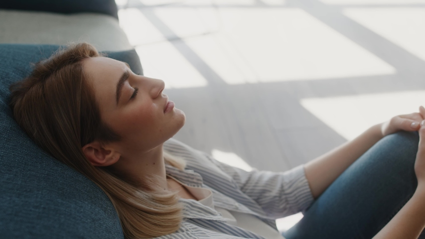 Serene attractive young woman resting on couch taking deep breath of fresh air, healthy calm lady relaxing on comfortable sofa napping feel stress free at home lounge alone sunny day sunlights | Shutterstock HD Video #1049027392