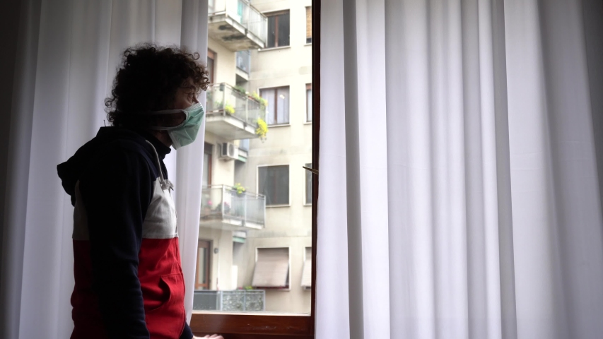 Europe, Italy, Milan - Man 40 years old at home in quarantine with mask looks out of the closed window to protect himself from the pandemic of n-cov19 Coronavirus                                     Royalty-Free Stock Footage #1049037997