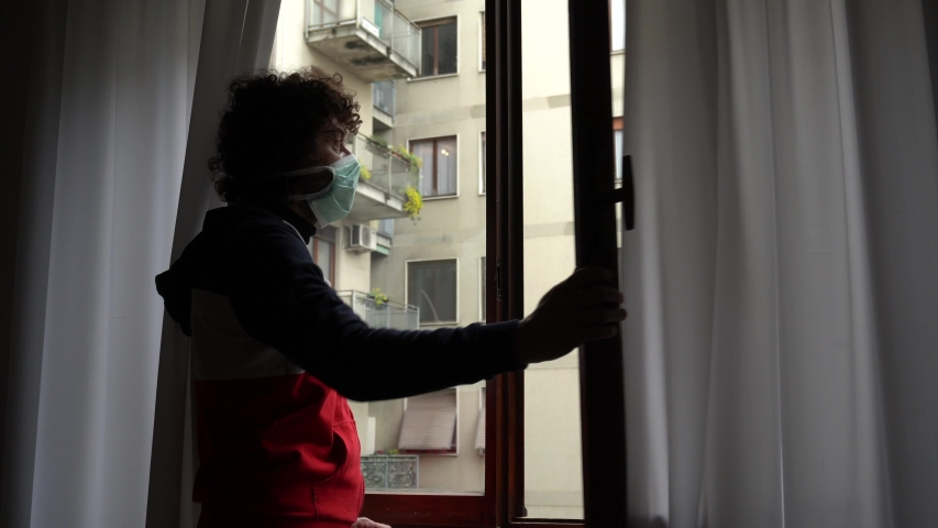 Europe, Italy, Milan - Man 40 years old at home in quarantine with mask plays music from  window -  pandemic of n-cov19 Coronavirus - Italian flash mob                                    Royalty-Free Stock Footage #1049038111