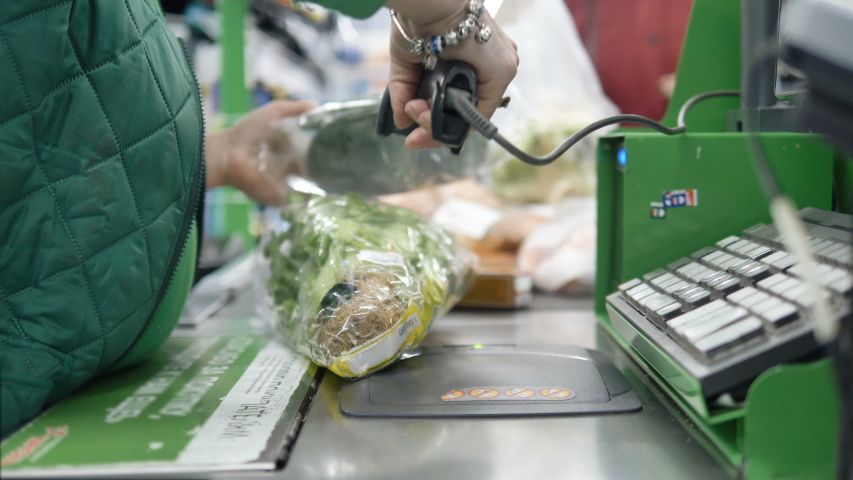 Cashier in a green sweater punching food at the checkout in a supermarket, close-up. Working at the cash register. Royalty-Free Stock Footage #1049038276