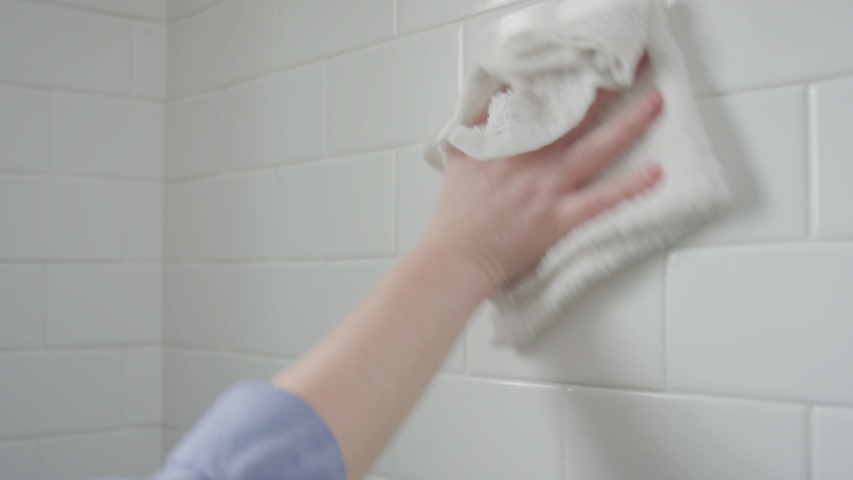 Closeup Of Woman Using Spray Bottle And Rag To Disinfect Her Bathroom Shower Subway Tiles | Shutterstock HD Video #1049043694