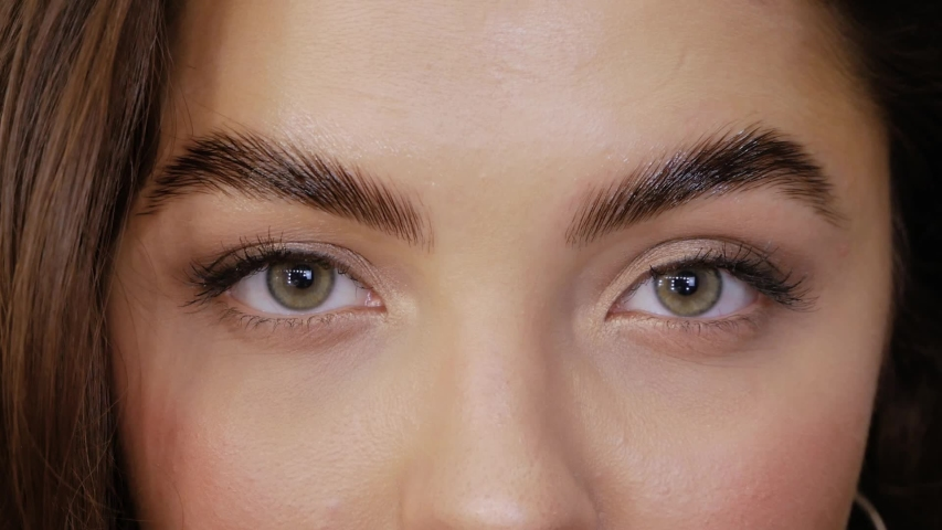 Cute girl with green brown eyes after Eyebrow Lamination Procedure close-up. Young woman looks straight into the frame and closes her eyes slow motion