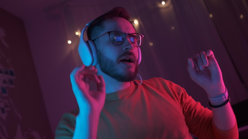 Portrait young handsome man in headphones listening energetic music at home. Bearded student with glasses relax in living room in colourful neon light. Dance hand movements to the rhythm. Indoors