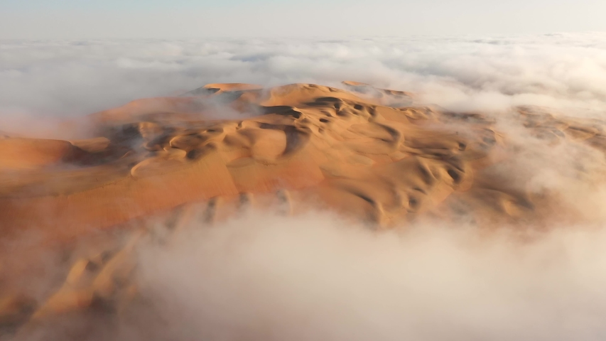 Aerial view of a drone flying over massive sand dunes covered by thick fog clouds at sunrise. Liwa desert, Abu Dhabi, United Arab Emirates. | Shutterstock HD Video #1049064520