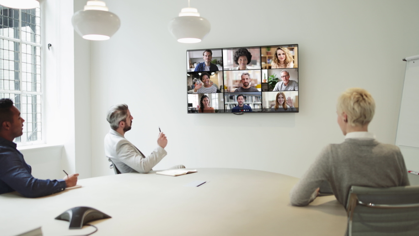 Group Using Video Conferencing technology in office for video call with colleagues abroad Royalty-Free Stock Footage #1049073499