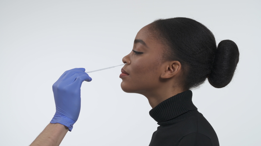 Coronavirus COVID19 nasopharyngeal swab guidance. Collecting DNA from the cells inside of nose using a flocked nasal swab. Side view of a young african american woman. Isolated on the white background Royalty-Free Stock Footage #1049078665