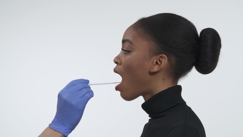 Coronavirus COVID19 buccal swab guidance. Collecting DNA from the cells inside of a cheek using a flocked tapered swab. Side view of a young african american woman. Isolated on the white background. Royalty-Free Stock Footage #1049078671