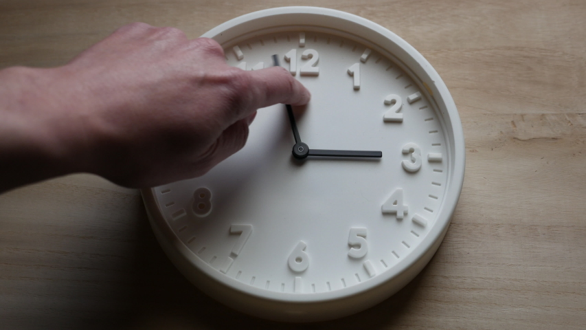 Daylight saving time ends, clock is turned backward by one hour by a man's hand Royalty-Free Stock Footage #1049083093