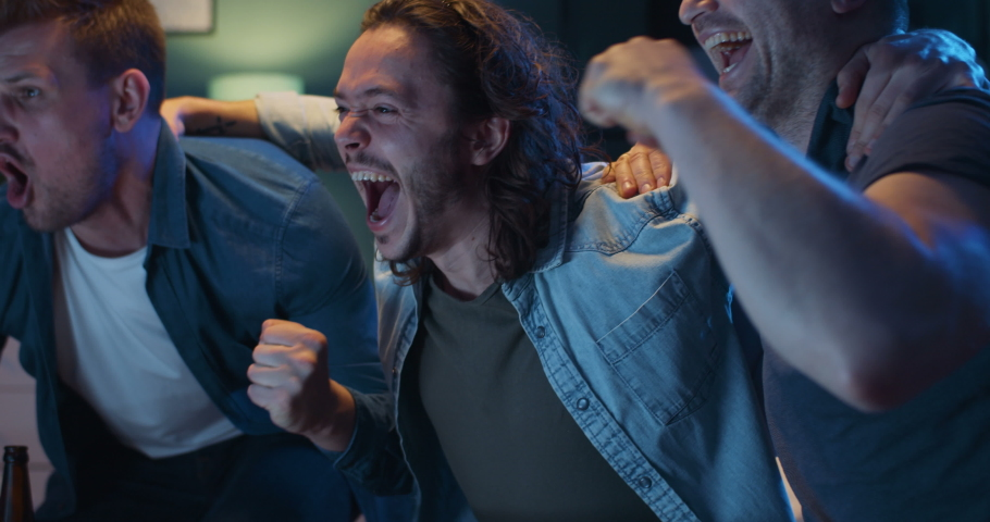 Close up of cheerful happy Caucasian guys cheering for favorite team and it scoring goal and winning game. Men watching TV with sport channel late at night and drinking beer.