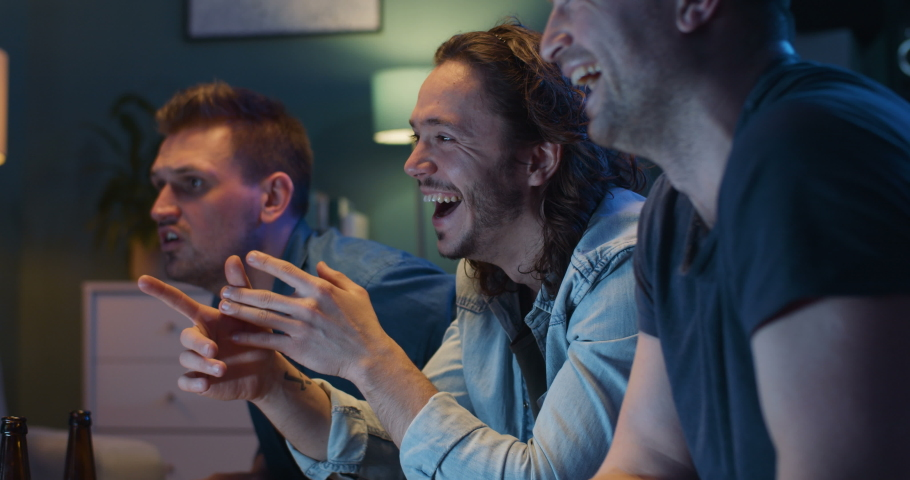 Close up of happy cheerful Caucasian men sitting on sofa in living room at night and watching comedy movie on TV. Joyful guys laughing. Male best friends spending time together. Royalty-Free Stock Footage #1049086375