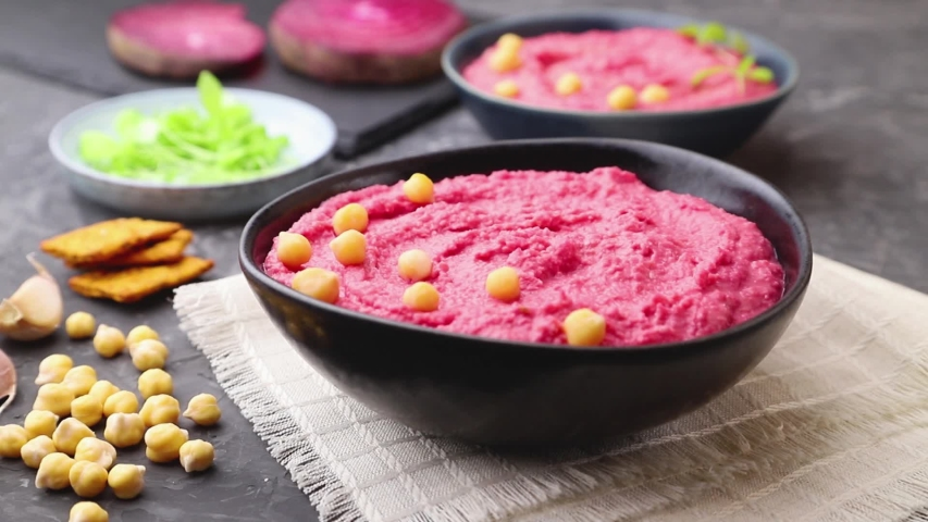 Hummus with beet  in blue ceramic bowl on a black concrete background and linen textile, decorated with microgreen basil sprouts by male hand. Side view, close up. | Shutterstock HD Video #1049086504