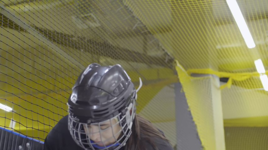 Low angle view of young brunette wearing hockey uniform standing in indoor hockey arena, taking off helmet and starting supporting her teammates | Shutterstock HD Video #1049092900
