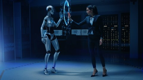 Beautiful, Confident Female Engineer Touching Hands with Humanoid Robot Activating Collaboration, Teamwork Protocol. Computer Artificial Intelligence Concept: People and Robots Working Together