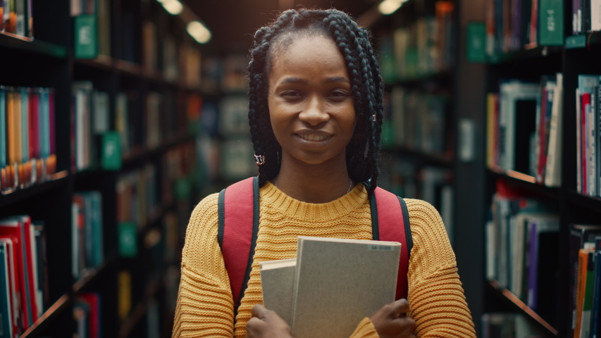 University Library: Smart Beautiful Black Girl Standing Next to Bookshelf Holding and Reading Text Book, Doing Research for Her Class Assignment and Exam Preparations. Authentic Students Study and Suc