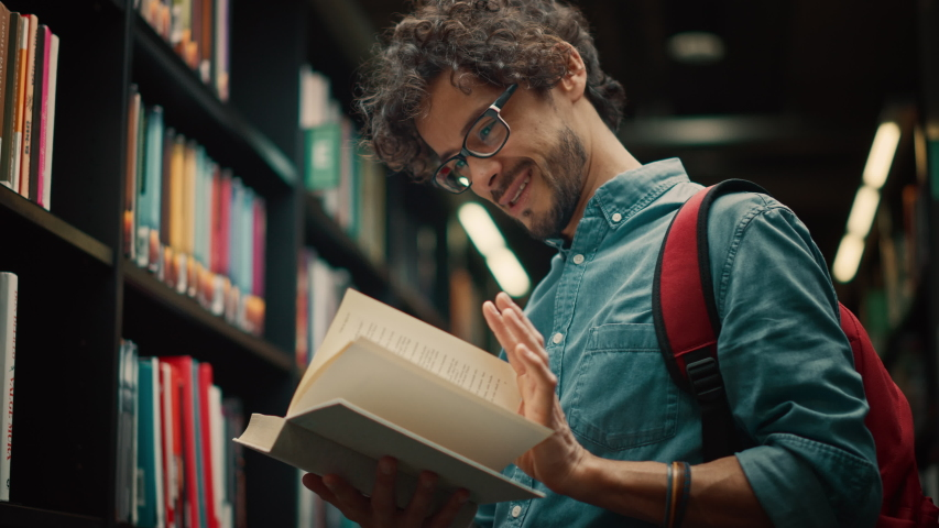 University Library: Talented Hispanic Boy Wearing Glasses Standing Next to Bookshelf Reads Book for His Class Assignment and Exam Preparations. Low Angle Portrait Royalty-Free Stock Footage #1049094829