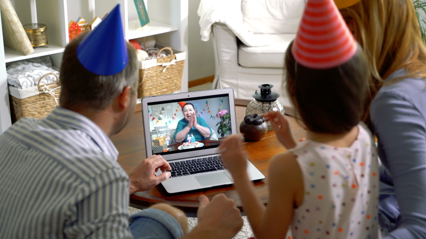 A family with a child congratulating a grandmother on her birthday using a video call. Home quarantine, social distancing, self isolation. #1049104063