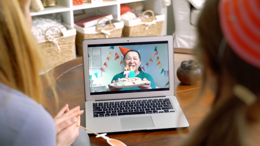 A family with a child congratulating a grandmother on her birthday using a video call. Home quarantine, social distancing, self isolation. Royalty-Free Stock Footage #1049104084