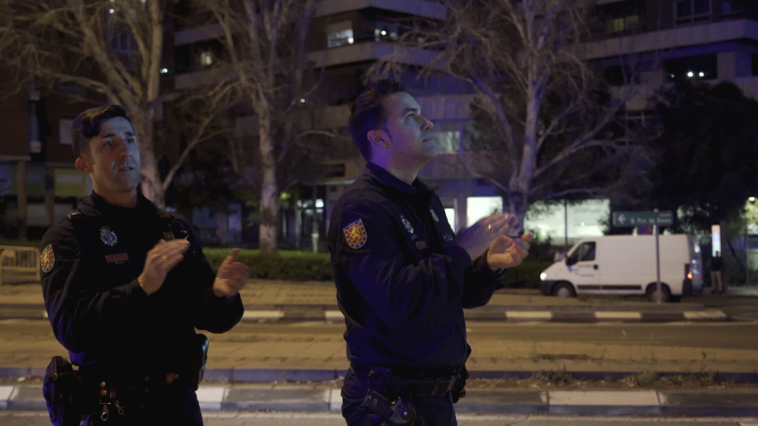MADRID, SPAIN – MARCH 25 2020. Two National Police officers applaud medical workers from the Fundacion Jimenez Diaz hospital who are fighting coronavirus