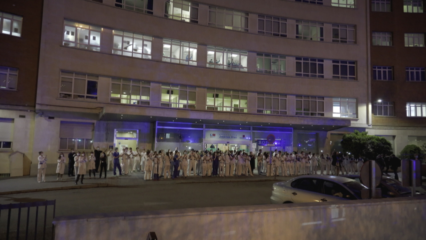 MADRID, SPAIN - MARCH 25 2020. Medical staff from the Fundacion Jimenez Diaz hospital who are fighting coronavirus applaud back the people of Madrid and police officers for their support