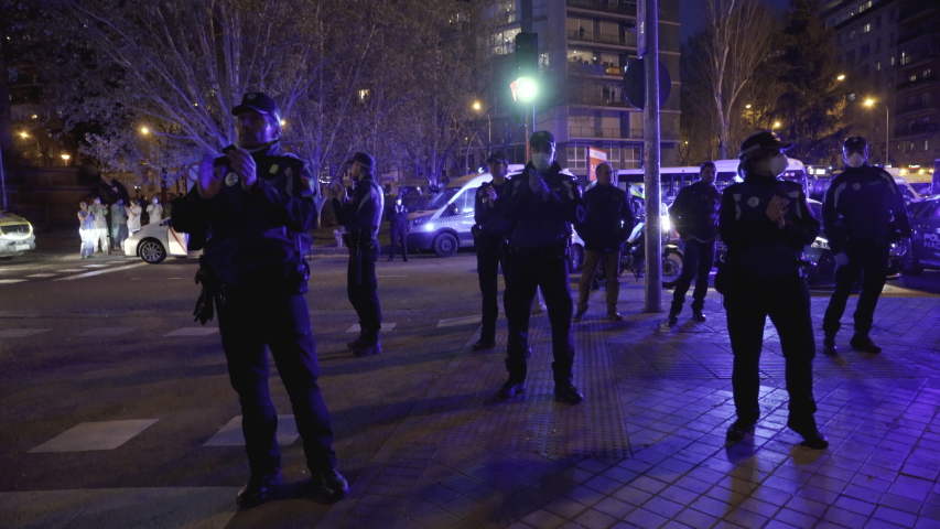 MADRID, SPAIN – MARCH 25 2020. A group of Madrid Municipal Police officers applaud medical workers from the Fundacion Jimenez Diaz hospital who are fighting coronavirus