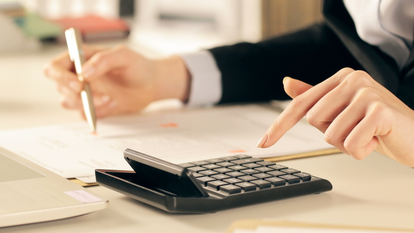 Close up of executive hands doing accounting using calculator comparing document at office Royalty-Free Stock Footage #1049115040