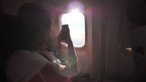 A girl takes pictures of beautiful landscapes from the airplane window using her phone.