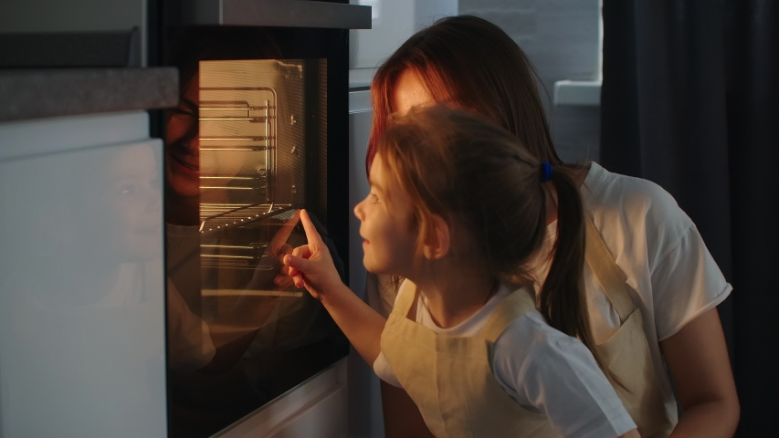 Mother Mother and daughter watch as a pie is prepared in the oven. Happy childhood. Make homemade pizza together #1049119084