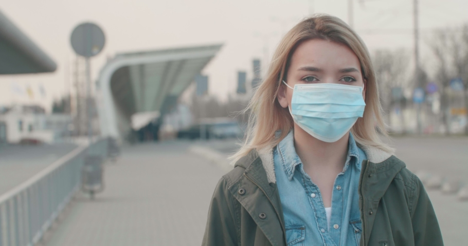 Young blonde Woman wearing a Protective Mask against infectious Diseases, walking near Bus Station. Pandemic Coronavirus2020. The concept health and safety, N1H1 coronavirus, virus protection. | Shutterstock HD Video #1049122336