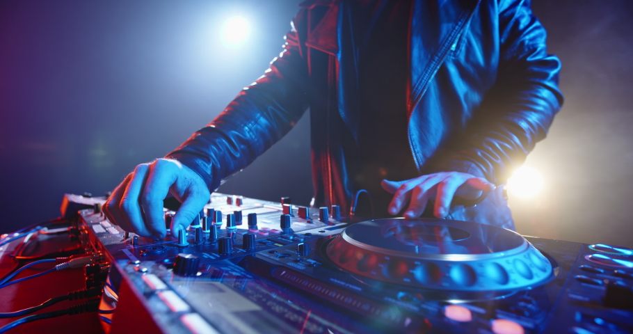 A cool bearded dj standing at the mixer controller, composing a new mix and rocking the party in a nightclub - nightlife concept 4k footage | Shutterstock HD Video #1049137939