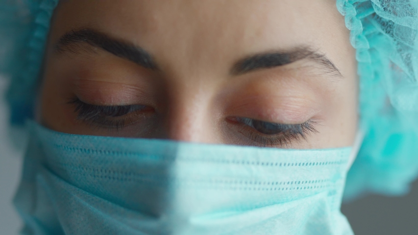 Sad and tired medic opens eyes and looking atraight at camera. medical stuff portrait closeup. Woman in Protective Face Mask,