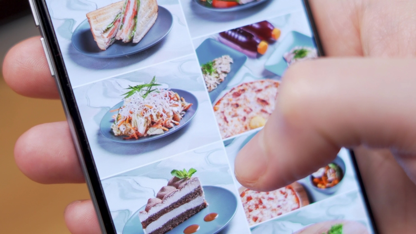 A Man Chooses Food with Delivery in the App of an Online Food Store Using a Smartphone. Close- Up of the Smartphone and Hand. Krasnodar March 2020