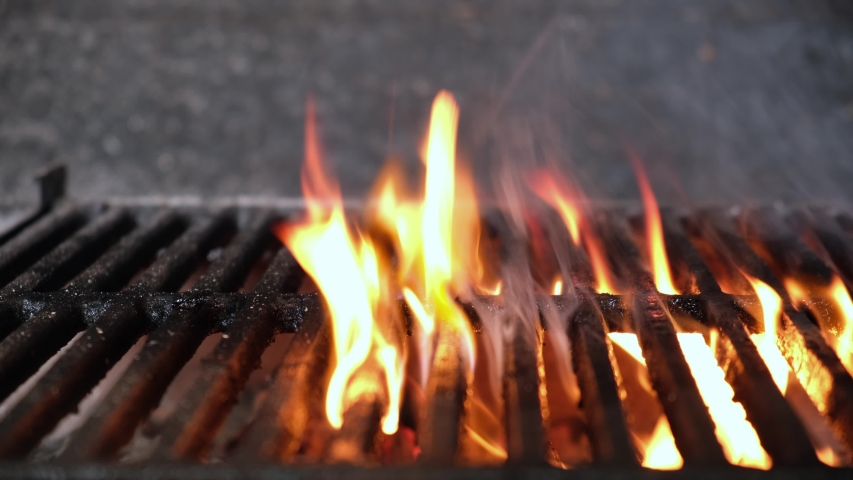 Empty hot charcoal barbecue BBQ grill with a large flame of fire and smoke is burning in restaurant. Dolly sliding video | Shutterstock HD Video #1049146579