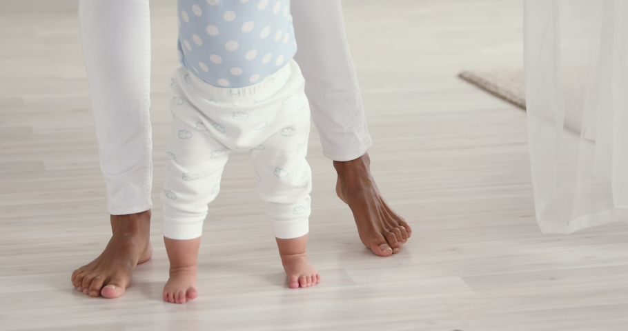 Infant barefoot baby girl boy learning to walk standing on warm floor. African american mum holding hand helping cute little child making first steps at home. Underfloor heating concept, close up view | Shutterstock HD Video #1049156362