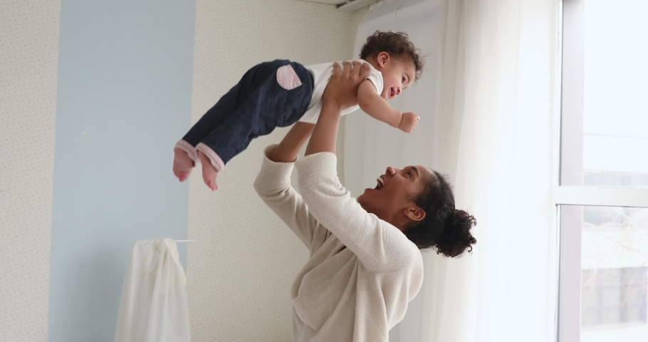 Happy young adult african american mom holding cute adorable infant child girl lifting up standing in bedroom. Cheerful adult mommy playing with cute funny kid baby boy having fun together indoors.