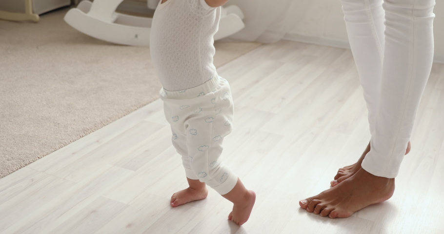 Cute barefoot small mixed race baby girl learning to walk holding mom hands. Funny adorable african infant toddler child daughter playing with mum making first step on warm heated floor. Close up view | Shutterstock HD Video #1049156416