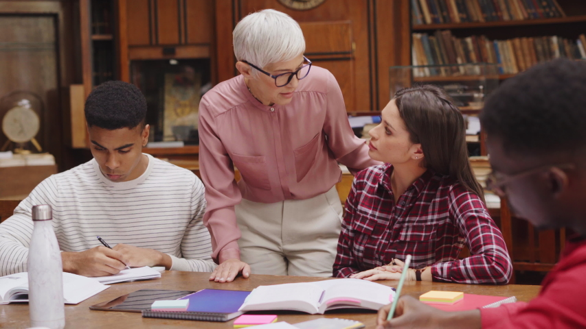 Senior woman teacher working with college students in library. Graduates consulting with their lecturer informally during a break in library. Group of students studying with their professor. Royalty-Free Stock Footage #1049156923