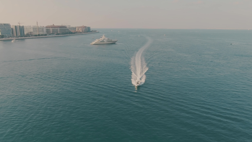 Aerial view of cruising motorboat and unknown anchored luxury motor yacht offshore in Dubai, UAE