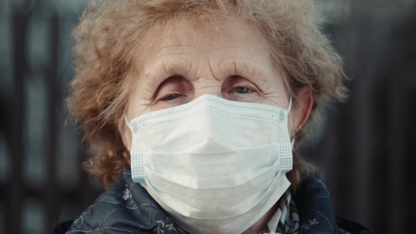 elderly woman in a respirator protection mask is walking the street. Quarantine coronavirus covid-19 for old people. Retirement Health at Risk, granny in mask Royalty-Free Stock Footage #1049181181