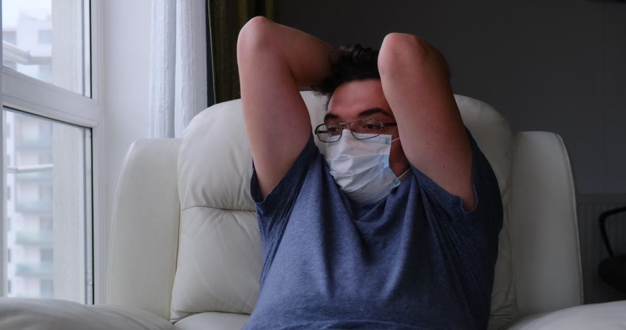 Man with medical mask sits in armchair next to a window, looks outside, runs his fingers through his hair in despair, while quarantined at home.