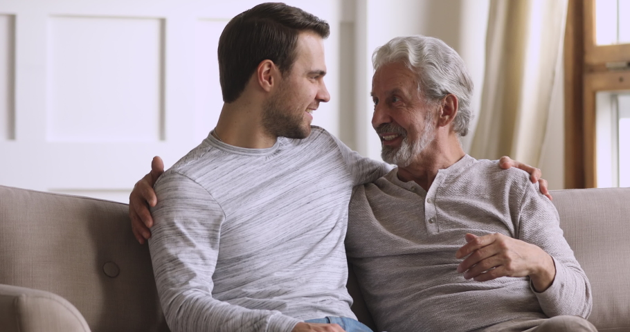 Smiling young man cuddling elderly senior father, holding sincere trustful conversation in living room. Bonding happy two different male generations family communicating talking chatting at home.