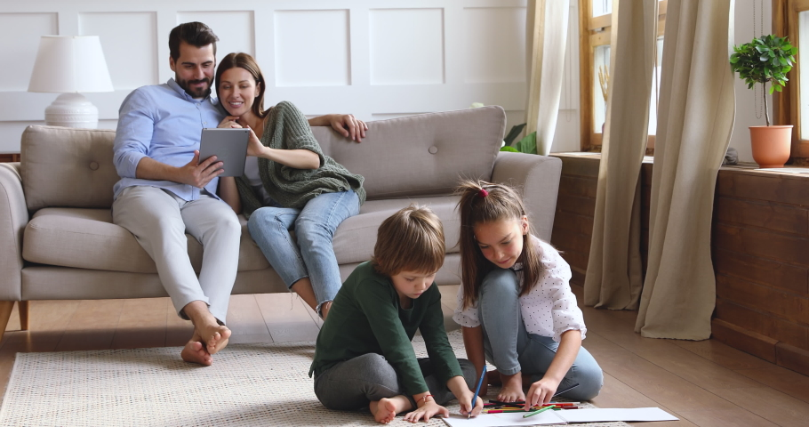 Happy young couple resting on sofa, watching funny movie online on tablet while small children siblings coloring drawing pictures in paper album, sitting together on floor carpet in living room.