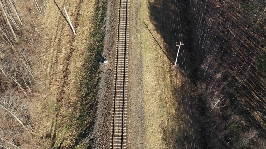Railway in the forest in autumn. Top view. Aerial drone shot over railway and fores. Aerial view of railroad in beautiful forest. Transportation. Aerial view of moving commuter train in fall.    | Shutterstock HD Video #1049194570