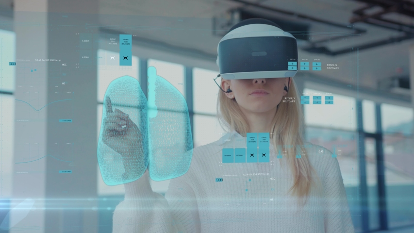 Augmented Reality. Close-up of a Female Doctor Looking: Medical Charts, 3D Hologram (DNA hologram, Pulmonary System, Muscular System, COVID-19) Wearing VR Glasses and Headsets. Future Medicine. VR Royalty-Free Stock Footage #1049197141